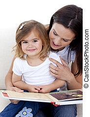 Little girl reading a book withher mother in living-room