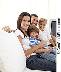 Happy parents and children sitting on sofa at home