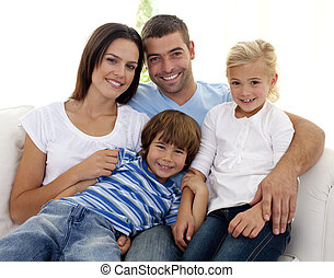 Smiling young family sitting on sofa at home