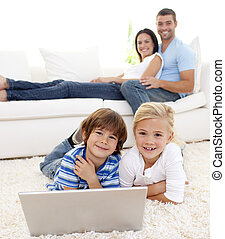 Children playing with a laptop and parents lying on sofa -...