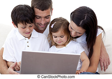 Young family using a laptop at home