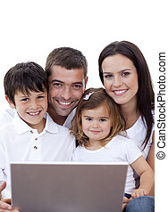 Portrait of young family using a laptop at home - Portrait...