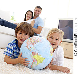 Children playing with a terrestrial globe at home with their...
