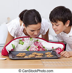 Mother and son smelling home-made biscuits in the kitchen