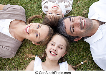 Smiling family lying in a park with heads together