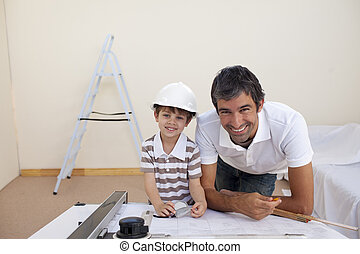Smiling dad and little boy studying architecture at home