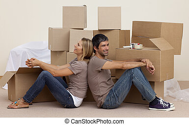 Happy couple sitting on floor unpacking boxes after moving...