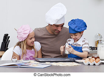 Father and children baking in the kitchen - Smiling father...
