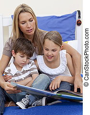 Mother reading a book with her children