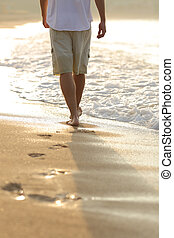 Back view of a man legs walking on the beach