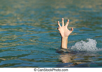 Hand of a man drowning in the sea