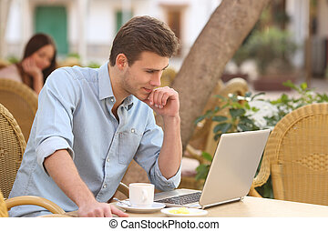Self employed man working with a laptop in a restaurant -...