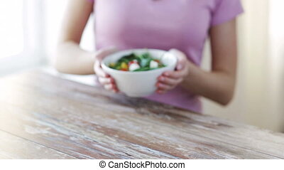 close up of young woman hands showing salad bowl - healthy...