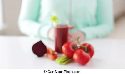 close up of woman hands with juice and vegetables - healthy...
