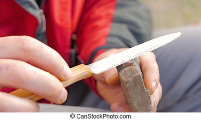 Adult caucasian man sharpening the knife - Adult caucasian...