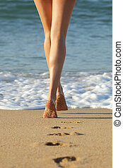 Woman legs walking on the sand of the beach towards the sea...