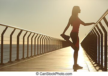 Woman silhouette exercising stretching on a bridge after...