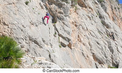 Caucasian person rock climbing - Caucasian woman climbing...