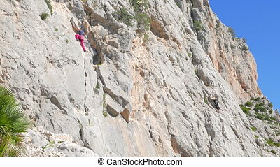 Caucasian person rock climbing - Caucasian woman climbing up...