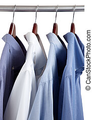 Blue dress shirts on wooden hangers - Assorted blue dress...