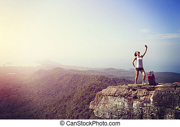 hiker taking photo with smart phone - young woman hiker...