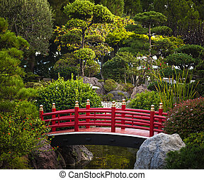 Red bridge in Japanese garden - Red bridge over pond in...