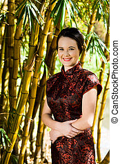 woman by bamboo plant - a pretty young girl in dress...