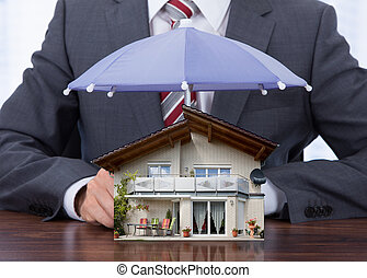 Businessman Sheltering House With Umbrella - Midsection of...