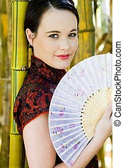 elegant asian woman - an elegant asian woman with a fan by...