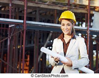 female architect - mid adult architect holding blueprints...