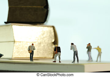 Creative idea concept - miniature photographer with vintage golden book on open paper notebook