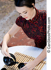 chinese tea ceremony - a woman performing the chinese tea...