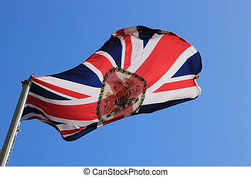British Embassy flag flying in the wind against a blue sky....