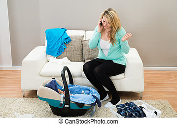 Woman Talking On Mobile Phone With Laundry Clothes In Living...