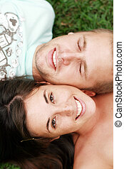 teen couple - a teen couple lying with their heads together...