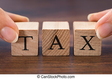 Person Hand Holding The Word Tax - Close-up Of Person Hand...