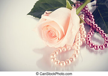 Pink rose and pearl beads. - Flower of a pink rose and pearl...