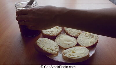smearing jam bread for breakfast and a plate of porridge -...