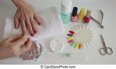 Manicure process in salon Cleaning gel nail polish to cover...