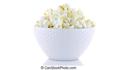 Popcorn in a white bowl on a white background