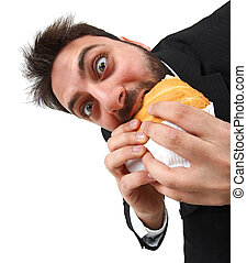 Young man while eating quickly a sandwich on white...