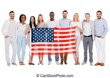 Team of America. Full length of happy diverse group of people bonding to each other and holding flag of America while standing against white background together