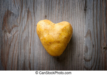 Heart shaped golden potato spud on Wooden Table Background,...