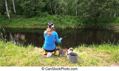 woman fish pond and cat - Young blond woman fishing on pond...