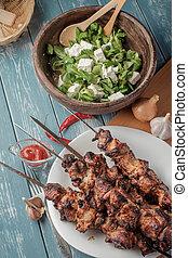 Shashlik with salad on the wooden table. - Shashlik with...