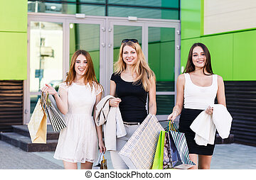 Young women after shopping - Three young women walking on a...