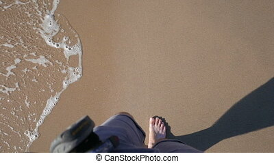 Walking in the sand - Young caucasian man walking on the...