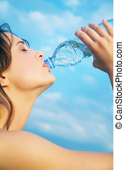 Woman With Mineral Water - Young woman outdoor against blue...