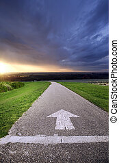 Ready to start - Asphalt road with arrow and sunset in...