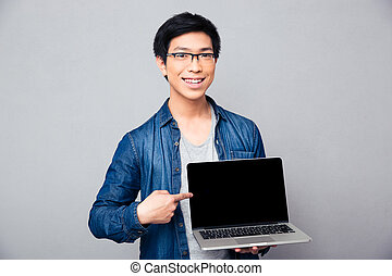 Smiling handsome asian man showing on laptop screen -...